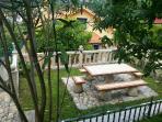 Vista desde jardín superior a la mesa exterior, balaustre de piedra y casa.