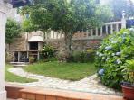 Vista del jardín, barbacoa y balaustres de piedra.