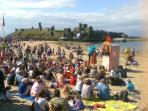 Watch Punch & Judy on the beach, with the ancient castle in background where sunsets appear late