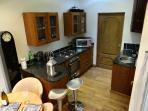 A view into the well equiped kitchen area with small breakfast bar with  F/F washer and dryer.