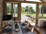 The dining area at The Old Mill looks out onto the patio and garden beyond