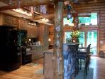 Kitchen with rustic hand peeled white pine logs/custom oak cabinets