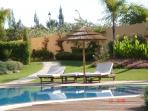 Sun loungers and shades around the pool