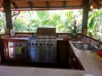 The outdoor kitchen has a Trader Vic's appeal with Viking appliances.