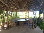 Breakfast area under makuti rondavel overlooking the pool