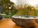 Enjoy a hot outdoor bath carved from volcanic rock on your private deck