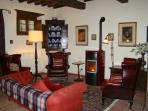 Comfortable leather chairs and sofa in the gracious sitting room with cosy stove