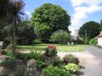 The gardens looks across the road to the medieval parish church and off road parking