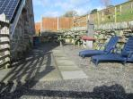 Patio area at the back with BBQ, sun loungers and picnic bench.
