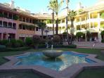 Apartment (centre) viewed from Plaza de las Palmeras fountain & garden in the evening sun.
