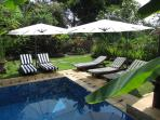 Private pool with deck chairs and cantilevered shade umbrellas