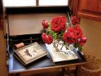 Desk with information book for guests and  roses from garden