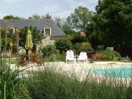 The pool is landscaped and surrounded by countryside.