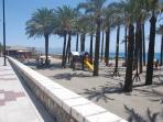 Paseo marítimo cercano al apartamento. Palmeras, zona de juegos infantil, arena, playa y sol.