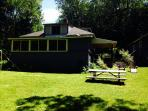 Back of House with Picnic Table and Adirondack Chairs