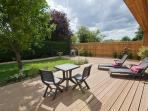 The spacious south-facing decking is equipped for outdoor dining and lounging in the sun