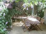 A private, secluded patio surrounded by vines & trees, for dining al fresco