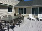 The large deck with the sun room in the background. Seats around 13 people.