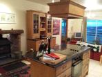 Kitchen features a multi-fuel stove and centre island with oven and electric hob.