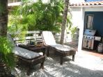 Tropical shaded rear yard with lounges and full size BBQ grill