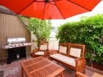 Shaded patio with greenery and private BBQ