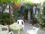 Vine and wisteria covered patio with table & chairs and a gas barbecue.A shady retreat in summer.