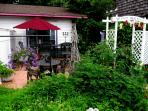There is a charming iron cocktail bar and seating on the front patio among the tomato plants.