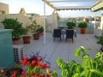 Vacker takterrass med matplats, solstolar, grill och grönska