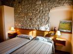 Habitación con dos camas juntas , baño, televisión y aire acondicionado