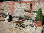 The garden is a real sun-trap, bordered by yew hedging and a brick and flint wall