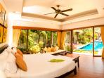 Main bedroom with views to the pool and tropical garden