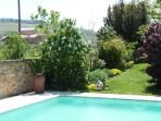 Private swimming pool sheltered by a wall set in the scenic garden within view of the house.