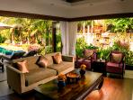 Living room open to pool deck and tropical gardens