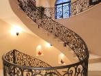 A SPIRAL ORNAMENTAL WROUGHT IRON STAIRCASE.
