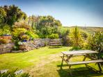 Tresillian has a large sheltered walled garden with lush plants and generous garden furniture