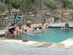 boys in pool with shaded outside dinning area seating 16