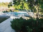 View of the heated pool through large french kitchen windows onto terrace
