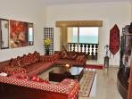 The Lounge Area, Large TV, with Arabic seating and door access to the balcony and direct sea views