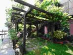The garden shady area under the bower. There are deckchairs cushions & chairs to eat outside.