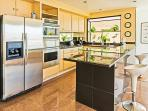Sunny kitchen with island workspace and additional breakfast bar seating for 2.