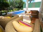 Outdoor lounge with rattan luxury furniture. Just birdsong and cool breezes to relax by the pool.