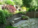 Enclosed rear garden with dry-stone walling and built-in seating