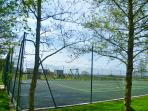 Our all weather well maintained doubles tennis court with play area beyond