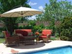 Patio furniture is shaded with large umbrellas