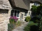 The sunny, south-facing aspect to the cottage edged with country garden plants and flowers.
