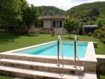 Vista del giardino e della piscina dal gazebo, in secondo piano il casale.