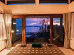 Bedroom romantically lit at evening time with outstanding ocean views