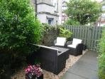 secluded patio area with Rattan sofa, 2 chairs and coffee table, addition patio table and 6 chairs