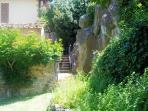 The apartment is reached by a lovely terraced staircase with flowers cascading from the rocks