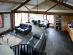 View over living area from oak staircase leading to upstairs double bedroom with ensuite
